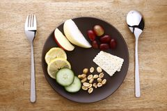 Fruits, vegetables, nuts and crackers on a plate Stock Photos