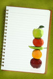 Fruits and vegetables on notebook page Royalty Free Stock Photography
