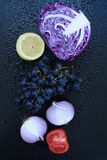 Fruits and vegetables. Red cabbage, lemon, grapes. onions and tomato on dark background Stock Image