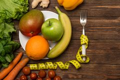 Fruits and vegetables on rustic wooden backround with space for text. Healthy eating, dieting, slimming and weigh loss concept. Ve Stock Images