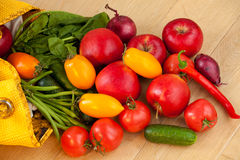 Fruits and vegetables spilling out of a yellow bag royalty free stock photos