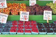 Fruits and vegetables Stall Berries Display. Blueberries Raspberries Grapes Cherries Blackberries Display with Signage at Fruit and Vegetable Stand Royalty Free Stock Photo