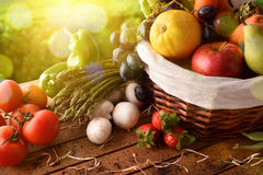 Fruits and vegetables on table and crop landscape background ele Royalty Free Stock Photos