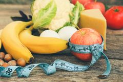 Fruits and vegetables, tape measure on old wooden background. Concept of proper nutrition. Royalty Free Stock Photos
