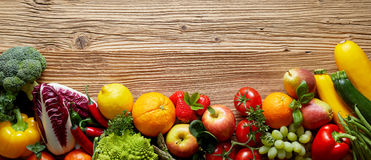 Fruits and vegetables on wooden table. Fresh fruits and vegetables mix on wooden table surface with unpainted woodgrain copy space above in the wide frame royalty free stock photos