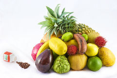 Fruits versus multivitamins. Concept of various tropical fruits against multivitamin tablets isolated on a white background Stock Images