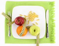 Fruits, vitamins and measuring tape. Diet concept. Fruits and vitamins with measuring tape on a plate Stock Image