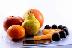 Fruits vs sweets on scale Stock Photo