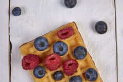 Fruits in a waffle. Different berries on a waffle and in a bowl on a white wooden table Royalty Free Stock Photos