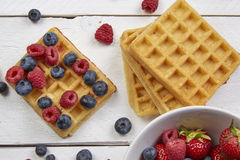 Fruits in a waffle. Different berries on a waffle and in a bowl on a white wooden table Stock Images
