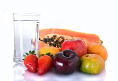 Fruits and water. Some fruits with glass of water isoated Royalty Free Stock Image