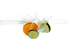 Fruits in water. Fresh fruits (cucumber and orange) in cold water and splash Stock Photo