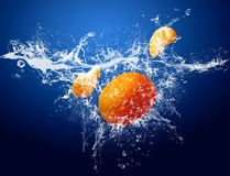 Fruits in water. Drops around fruits on blue background stock photo