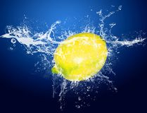 Fruits in water. Drops around fruits on blue background royalty free stock photo