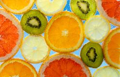 Fruits in water. Orange,lemones,kiwi and grapefruit in water with bubbles on blue background Stock Photo