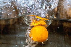 Fruits in water, aquashake, orange. An orange floating in water and bubbles Stock Photo