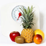 Fruits with a weight scale. Fruits isolated on white with a weight scale on the background / concept of fruit dieting and healthy lifestyle Stock Photos