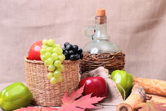 Fruits, wine and autumn leaves Stock Photos