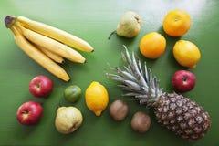 Fruits on the wood background. Fruits on the wood green background. Pineapple, orange, lemon etc Stock Photo