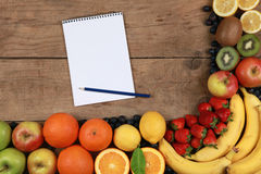 Fruits on a wooden board with notebook Stock Images