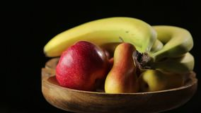 Fruits on a Wooden Plate pan right. Fruits on a wooden plate on the black background pan to right stock footage
