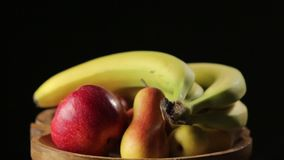 Fruits on a Wooden Plate. On the black background tilt down stock video footage