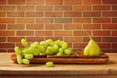 Fruits on wooden table over brick wall Stock Images
