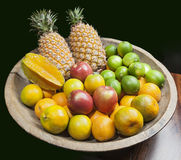 Fruits in woody tray. Pineapple, apple, star fruit, lemon and orange in woody tray Royalty Free Stock Photos