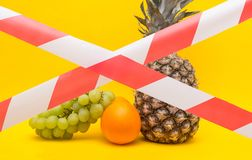 Fruits on a yellow background behind a protective red ribbon, a ban on the importation of fruits and food products, sanctions. Prohibition stock photos