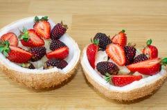 Fruitsalade, bessen, aardbeien, braambessen, ananas in kokosnoot Op de houten vloer stock fotografie