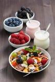 Fruitsalade, verse bessen en yoghurts op een houten lijst royalty-vrije stock foto