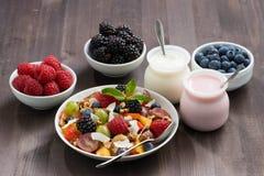 Fruitsalade, verse bessen en yoghurts op een houten lijst Royalty-vrije Stock Afbeeldingen