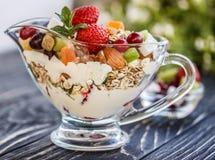 Fruitsaladeclose-up met bessen, yoghurt en granola in een glasboog Royalty-vrije Stock Foto's