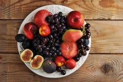 Fruitschotel - druiven, fig., perziken, peren, kersen op een hout Stock Fotografie