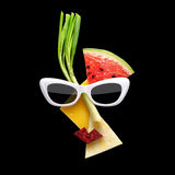 Fruity art. Quirky food concept of cubist style female face in sunglasses made of fresh fruits on black background stock photo