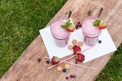 Fruity berry milkshake outdoors Stock Photos