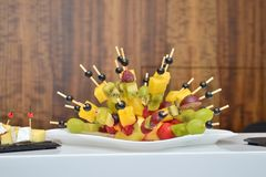 Fruity canapes in the form of a hedgehog at a banquet on the table on wooden background royalty free stock image