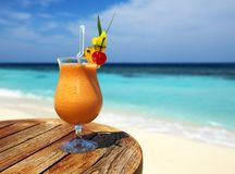 Fruity cocktail. Bocal of fruity cocktail on a beach table Stock Photo