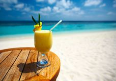 Fruity cocktail. Bocal of fruity cocktail on a beach table Royalty Free Stock Images