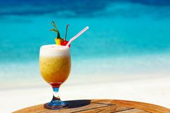 Fruity cocktail. Bocal of fruity cocktail on a beach table Royalty Free Stock Photography