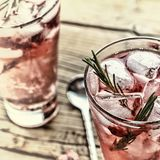Fruity cocktail drink decorated with frozen raspberry. Fruity cocktail drink decorated with frozen or fresh raspberry, strawberry, rosemary, ice and soda Royalty Free Stock Images