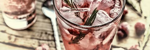 Fruity cocktail drink decorated with frozen raspberry. Fruity cocktail drink decorated with frozen or fresh raspberry, strawberry, rosemary, ice and soda Stock Photo