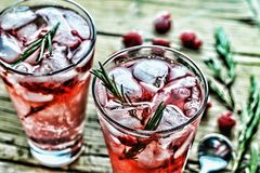 Fruity cocktail drink decorated with frozen raspberry. Fruity cocktail drink decorated with frozen or fresh raspberry, strawberry, rosemary, ice and soda Stock Images