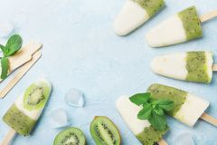 Fruity homemade ice cream or popsicles from kiwi smoothie and yogurt top view. Summer refreshing food. Stock Images