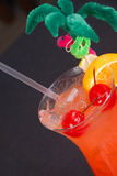 Fruity hurricane cocktail in tropical glass. Fruity hurricane cocktail in tropical glass with decorations, slice of orange, lime, and cherries Stock Photography