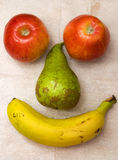 Fruity joy. Two apples, one pear and a banana colca in position to resemble features of a face Stock Photography
