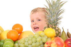 Fruity kid. 3-4 years old boy and lots of various fruits isolated on white royalty free stock image