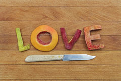Fruity Love. Letters made from fruit spelling the word Love on kitchen cutting board with fruit knife Stock Photography