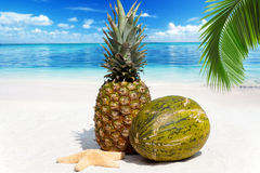 Fruity pineapple and melon. On the sandy beach with the blue sea in the background Stock Photo