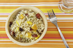 Fruity Quinoa Salad. Quinoa salad with dried fruit and colored peppers on a bright summer table cloth Royalty Free Stock Image